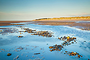 Pebbles zig-zag along Holme Beach at low tide. Holme dunes visible in the distance. North Norfolk, East Anglia.