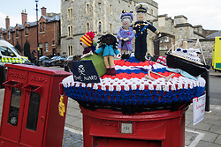 Windsor, UK. 16th April, 2021. A knitted postbox topper prepared by Ickenham Postbox Toppers and featuring the Queen and Duke of Edinburgh, the royal yacht Britannia and some Duke of Edinburgh award students is pictured in front of Windsor Castle on the eve of the funeral of Prince Philip.