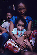 PENAN MOTHER AND CHILD, MALAYSIA. Sarawak, Borneo, South East Asia. Tropical rainforest and one of the world's richest, oldest eco-systems, flora and fauna, under threat from development, logging and deforestation. Home to indigenous Dayak native tribal peoples, farming by slash and burn cultivation, fishing and hunting wild boar. Home to the Penan, traditional nomadic hunter-gatherers, of whom only one thousand survive, eating roots, and hunting wild animals with blowpipes. Animists, Christians, they still practice traditional medicine from herbs and plants. Native people have mounted protests and blockades against logging concessions, many have been arrested and imprisoned.