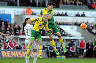 Norwich's Timm Klose (r) and Steven Naismith (c) beat Swansea's Federico Fernandez to the header. Barclays Premier league match, Swansea city v Norwich city at the Liberty Stadium in Swansea, South Wales on Saturday 5th March 2016.<br /> pic by  Carl Robertson, Andrew Orchard sports photography.