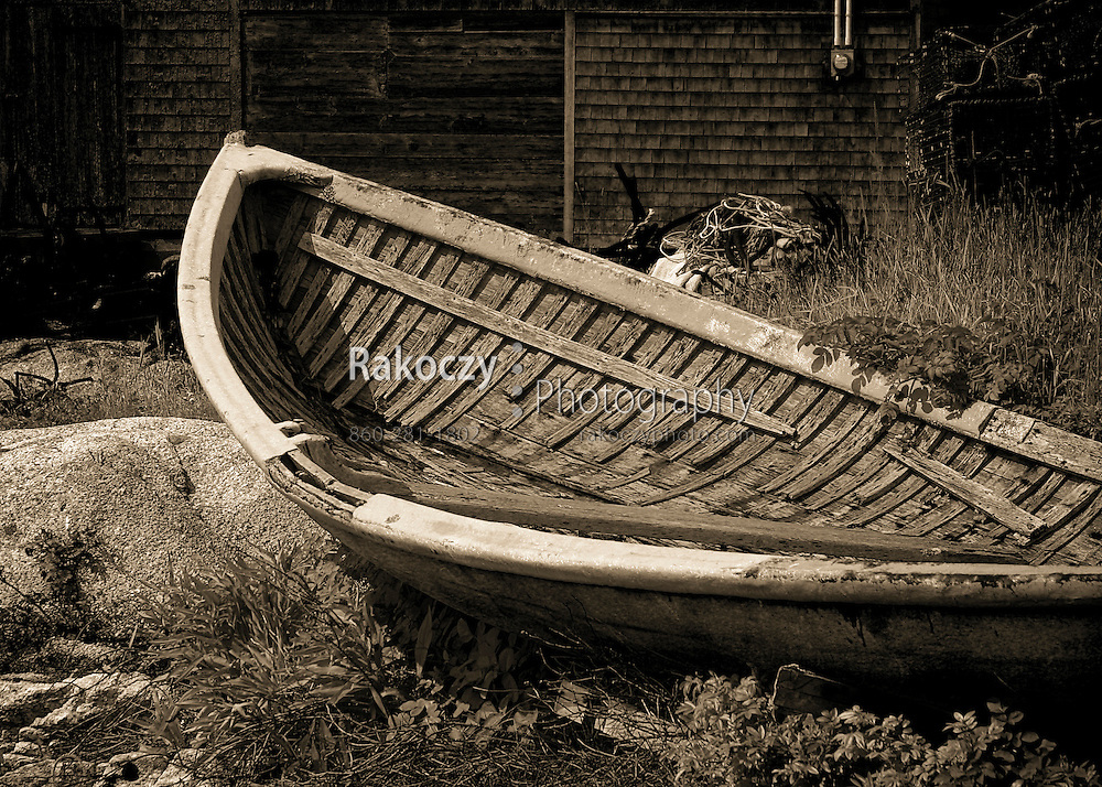 An old wooden boat decays on the ground near a weathered shack in Peggy's Cove in Nova Scotia, Canada