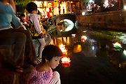 Children float flower shaped lanterns along a small waterway through the centre of Lijiang, Yunnan, China.