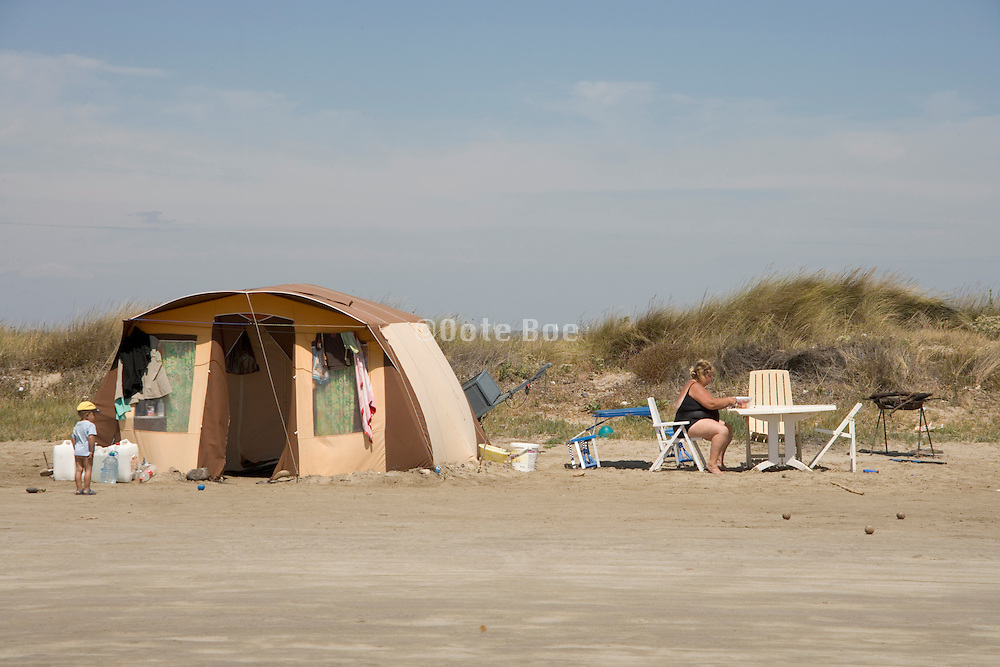a single large tent on a windswept beach with mother and child