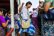 """17 JUNE 2013 - YANGON, MYANMAR:  Passengers get off the Yangon-Dala Ferry on the Yangon side. The ferry to Dala opposite Yangon on the Yangon River is the main form of transportation across the river. Every day the ferry moves tens of thousands of people across the river. Many working class Burmese live in Dala and work in Yangon. The ferry is also popular with tourists who want to experience the """"real"""" Myanmar. The rides takes about 15 minutes. Burmese pay about the equivalent of .06¢ US for a ticket.  Foreigners pay about the equivalent of about $4.50 US for the same ticket.   PHOTO BY JACK KURTZ"""
