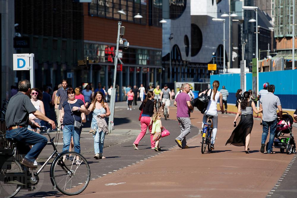 Nederland, Den Haag, 08-06-2014<br /> In Den Haag moet een vrouw op een OV-fiets uitwijken voor plotseling overstekende mensen op de Grote Marktstraat, een belangrijke winkelstraat. Alleen fietsers en voetgangers mogen hier komen. <br /> <br /> In The Hague a cyclists has to avoid suddenly crossing pedestrians at the Grote Markstraat. Only bicycles and pedestrians are allowed in this street.