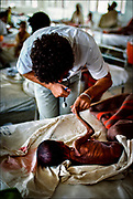 A doctor of the International Committee of the Red Cross examines a dying Ethiopian child--part of the ICRC's humanitarian work in an increasingly unstable world. The cause of the 1983-1986 famine is often ascribed to drought, but food shortages were the byproduct of an anti-government insurgency and the equally deadly government campaign against Ethiopian rebels.  © Steve Raymer / National Geographic Creative