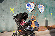 """16 OCTOBER 2020 - PERRY, IOWA: A woman with a child waits for a """"Get Out the Vote"""" event with Doug Emhoff, the husband of Vice Presidential Candidate Kamala Harris. Emhoff spoke to a group of about 30 people. The crowd was socially distanced and masks were required in  keeping with CDC and state of Iowa health guidelines to deal with the COVID-19 pandemic. Emhoff is traveling throughout Nebraska and Iowa today, campaigning on behalf of the Biden/Harris ticket.        PHOTO BY JACK KURTZ"""