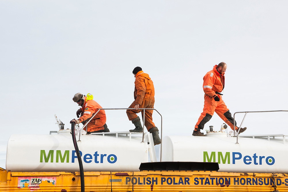 Krysztof Herman (l-r), Lukasz Gryglicki, and Robert Zmuda pump gasoline delivered by amphibious vehicle to storage tanks at the Polish Polar Station in Hornsund, Svalbard. The station operates year round and uses 90,000 liters of gasoline per year to operate generators, boats, snowmobiles, and heavy machinery.