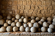 Tipoli, Lebanon - September 7, 2010: Centuries-old stone cannon balls stacked against a stone wall in an entryway at the historic Tripoli Citadel, which has been used by Muslims, Crusaders, and others before that. The Citadel is open to tourists, though part of the Citadel is a military post and thus off-limits.