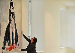 """© under license to London News Pictures. LONDON, UK  05/05/2011. A gallery worker positions the tapestry 'The Black Cat' by Tracy Emin which took seven years to complete.  The unveiling today (5 May 2011) of Tracey Emin's first tapestry ahead of the launch of COLLECT, the Crafts Council's international craft fair for contemporary objects at the Saatchi Gallery, London. Tracy Emin say's: """"The Black Cat is one of my favourite paintings. It took me seven years to complete...""""Photo credit should read Stephen Simpson/LNP."""