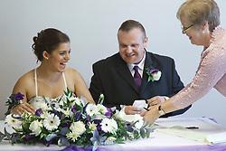 Bride who has cerebral palsy, with groom and registrar at wedding ceremony.