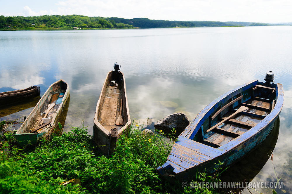Three traditional wooden boats and canoes beached on the shore of Lake Peten Itza in Flores in northern Guatemala.