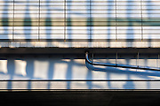 Reflections of an office building`s  windows on part of the expressway overpass system that snakes through Tokyo, Japan. Friday November 14th 2014