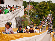 """15 JULY 2011 - PHRA PHUTTHABAT, SARABURI, THAILAND:  People walk up the stairs to Wat Phra Phutthabat in Saraburi province of Thailand, Friday, July 15. Wat Phra Phutthabat in Phra Phutthabat, Saraburi, Thailand, is famous for the way it marks the beginning of Vassa, the three-month annual retreat observed by Theravada monks and nuns. The temple is highly revered in Thailand because it houses a footstep of the Buddha. On the first day of Vassa (or Buddhist Lent) people come to the temple to """"make merit"""" and present the monks there with dancing lady ginger flowers, which only bloom in the weeks leading up Vassa. They also present monks with candles and wash their feet. During Vassa, monks and nuns remain inside monasteries and temple grounds, devoting their time to intensive meditation and study. Laypeople support the monastic sangha by bringing food, candles and other offerings to temples. Laypeople also often observe Vassa by giving up something, such as smoking or eating meat. For this reason, westerners sometimes call Vassa the """"Buddhist Lent."""" The tradition of Vassa began during the life of the Buddha. Most of the time, the first Buddhist monks who followed the Buddha did not stay in one place, but walked from village to village to teach. They begged for their food and often slept outdoors, sheltered only by trees. But during India's summer rainy season living as homeless ascetics became difficult. So, groups of monks would find a place to stay together until the rain stopped, forming a temporary community. Wealthy laypeople sometimes sheltered monks on their estates. Eventually a few of these patrons built permanent houses for monks, which amounted to an early form of monastery. Photo by Jack Kurtz / ZUMA Press  PHOTO BY JACK KURTZ"""