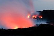 On the Big Island of Hawaii the lava hits the sea causing plumes of white smoke.
