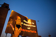 An anti-Morsi demonstrator holds a poster with a statement about US President Obama whilst putting his shoe over Obama's face, and a military helicopter flys overhead.cose to Tahrir Square, Cairo.