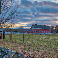 A rustic red barn as clouds catch the sunset color near Natick, MA in rural Massachusetts. Spring rains and colors have not quite moved into New England this year but the red barn, white fence, stone wall and colorful sunset sky made for a great composition and provided a classic setting for this tranquil moment in time. <br />