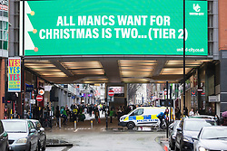 © Licensed to London News Pictures. 02/12/2020. Manchester, UK. A sign over Market Street, Manchester reads 'All Mancs want for Christmas is two... (Tier 2)' as the city enters Tier 3 restrictions. Photo credit: Kerry Elsworth/LNP
