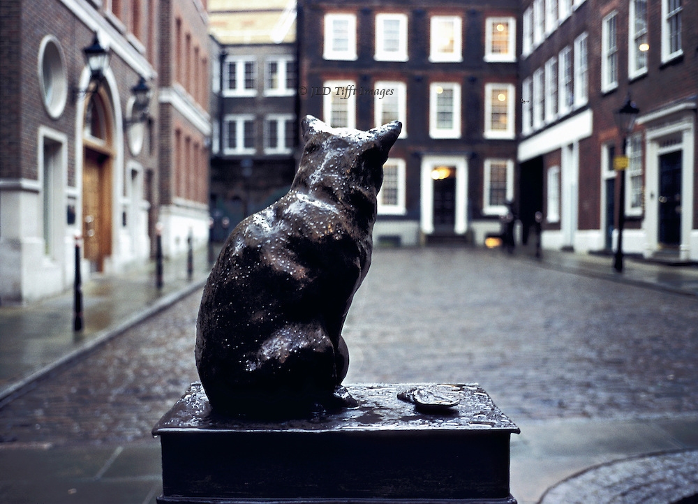 Bronze statue of Hodge, Dr. Samuel Johnson's cat, seated on his Dictionary (with an oyster) looks across Gough Square at Johnson's house.  Early evening lamps lit, rain-sodden cobblestones.  Rain drops sparkle on the cat's head, neck, and body too. Statue, by Jon Buckley, 1997.