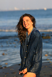 girlwearing a wet button down shirt by the ocean