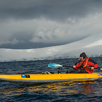 A kayaker paddles close to Wiencke Island, near the Antarctic Peninsula, Antarctica.  Anvers Island is in background.