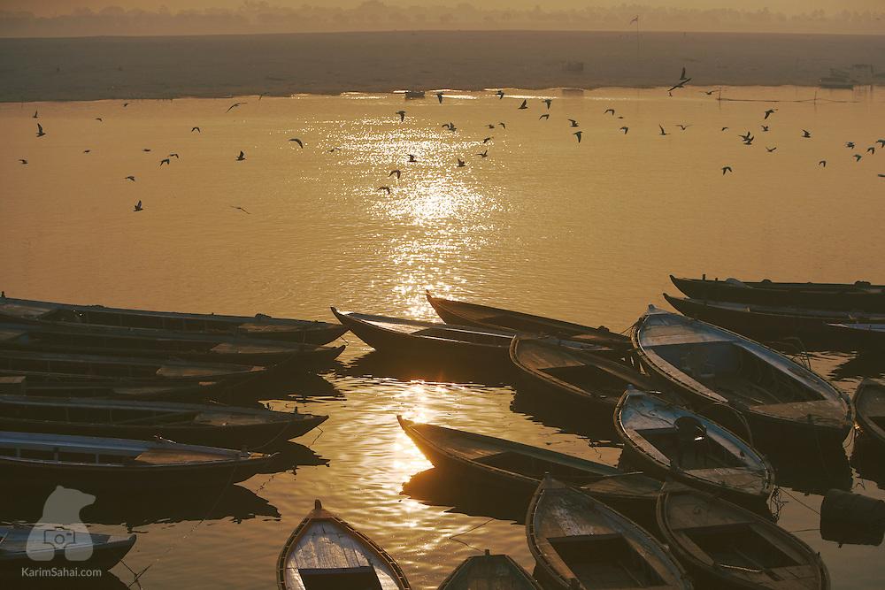 Wooden boats moored on the Ganges river at sunset, Varanasi, Uttar Pradesh, India