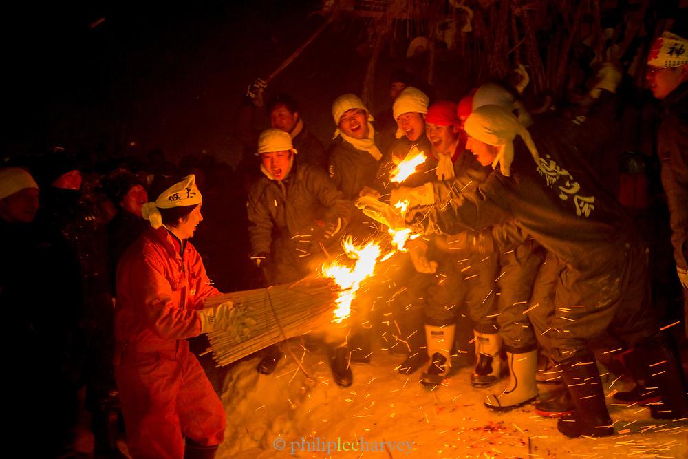Group of people burning straw at night, Nozawaonsen, Japan