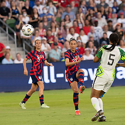 CHRISTEN PRESS (23) of the USA kicks the ball toward the goal to score for Team USA while Nigeria's ONOME EBI (5) defends  as the US Women's National Team (USWNT) beats Nigeria, 2-0 in the inaugural match of Austin's new Q2 Stadium. The U.S. women's team, an Olympic favorite, is wrapping up a series of summer matches to prep for the Tokyo Games.