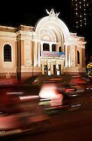 Blurred traffic movement around the Saigon Opera House at night.