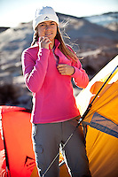 Woman wearing beanie and sports gear making a tent.