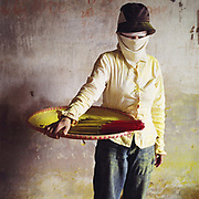 Portrait of a female worker covered in dust in Cao, a village specialising in making incense sticks, Hung Yen province, Vietnam. With Vietnam's growing population making less land available for farmers to work, families unable to sustain themselves are turning to the creation of various products in rural areas.  These 'craft' villages specialise in a single product or activity, anything from palm leaf hats to incense sticks, or from noodle making to snake-catching. Some of these 'craft' villages date back hundreds of years, whilst others are a more recent response to enable rural farmers to earn much needed extra income.