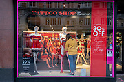 In advance of a re-opening of businesses and before a change to a Tier 2 for London during the second wave of the Coronavirus pandemic, a window dresser adjusts lingerie on mannequins in the window of erotic fashion retailer, Ann Summers on Oxford Street, on 30th November 2020, in London, England. Retailers will once again be open for Christmas business on 3rd December.