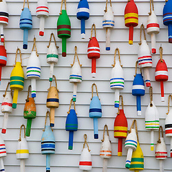 Wooden lobster buoys hang on a wall in Stonington, Maine.