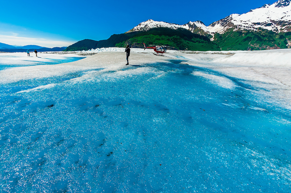 People with helicopter, meltwater pools on the Mendenhall Glacier, near Juneau, Alaska USA.