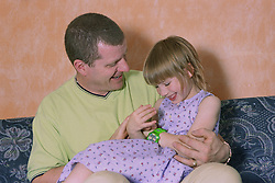 Father sitting at home on sofa holding young daughter,