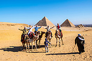 A family rides camels at the Giza Pyramid Complex, Giza, Egypt.