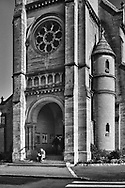Coffee cup in hand, a man is seated on the steps of St. Martin Church in Croissy-sur-Seine, France.  Aspect Ratio 1w x 1.5h.