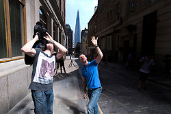 © London News Pictures. 04/09/2013. London, UK. A reporter from a television crew shades his eyes from the light as a camera man films the suns light as it reflects off 20 Finchurch Street in the financial district of central London. The building, which has been named unofficially the 'Walkie Talkie' building because of its shape, intensifies the suns light and reflects it onto the street below. There have been reports of damage to vehicles and local shops caused by the heat of the reflected light. Photo credit: Ben Cawthra/LNP
