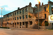 Building in Mostar damaged by the war and still not renovated. Ruined by bullet holes, mortar bomb shell grenade damage, very close to the beautifully renovated old town city centre. Along a busy main street in evening light with yellow street light giving an eerie atmosphere. Town of Mostar. Federation Bosne i Hercegovine. Bosnia Herzegovina, Europe.