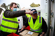 Victorian Trades Hall Council Secretary, Luke Hilakari (left) is seen helping a sheriff (right) unload a delivery of meat for the residents in the Alfred Street housing commission tower during COVID-19 on 10 July, 2020 in Melbourne, Australia. Former Federal Labor Leader Bill Shorten, along with close allies at Trades Hall help deliver Halal meat, supplied by Macca Halal Foods to the locked down housing commission towers following a coronavirus outbreak detected inside the complex. Mr Shorten was able to use his high profile to ensure food was not turned away by police so that it would reach the residents inside. (Photo be Dave Hewison/ Speed Media)