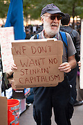 """A bearded man carries  a sign reading """"We don't want no stinkin' capitalism"""""""