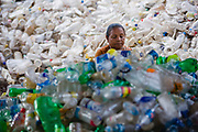 A woman emptying, sorting, crushing and removing the labels from plastic water and soda drink bottles before organising them for recycling, Tangra slum, Dhipi, Kolkata, India