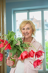 Portrait of mature woman holding vase with tulips, smiling