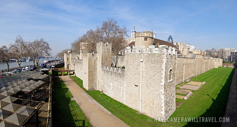 Wide angle shot of the Tower of London's exterior fortifications and moat, with the River Thames at left.