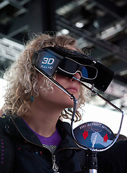 Woman looking at 3D television through 3D glasses at Photokina digital imaging trade show in Cologne Germany 2010