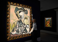 """© Licensed to London News Pictures. 14/06/2012. London, UK A gallery technician holds Pablo Picasso's """"Homme assis'  which is estimated to fetch 6-9MillionGBP. Photocall for Sotheby's June Impressionist and Modern Art Sale this June. Photo credit : Stephen Simpson/LNP"""