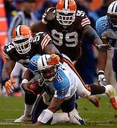MORNING JOURNAL/DAVID RICHARD.Cleveland defenders Andra Davis, middle, and Orpheus Roye, back, sack quarterback Steve McNair on a fourth-down play yesterday in the fourth quarter.