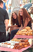 Sisters ages 24 and 17 selling baked goods at outdoor market.  Zakopane Poland