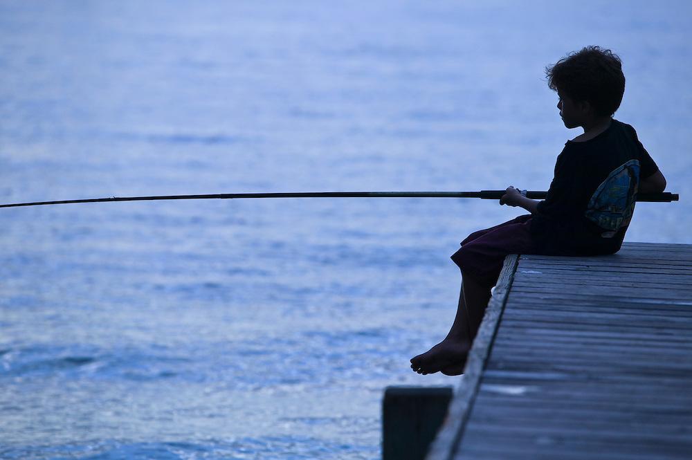 Fare, Huahine, French Polynesia, boy fishing on pier