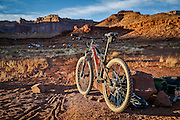 SHOT 10/16/16 5:56:58 PM - Tom Reynold's Orbea mountain bike parked for the evening at the Airport camping spot during the White Rim mountain biking trip in Canyonlands National Park just outside of Moab, Utah. The White Rim Road is a 71.2-mile-long unpaved four-wheel drive road that traverses the top of the White Rim Sandstone formation below the Island in the Sky mesa of Canyonlands National Park in southern Utah in the United States. The road was constructed in the 1950s by the Atomic Energy Commission to provide access for individual prospectors intent on mining uranium deposits for use in nuclear weapons production during the Cold War. Four-wheel drive vehicles and mountain bikes are the most common modes of transport though horseback riding and hiking are also permitted.<br /> (Photo by Marc Piscotty / © 2016)